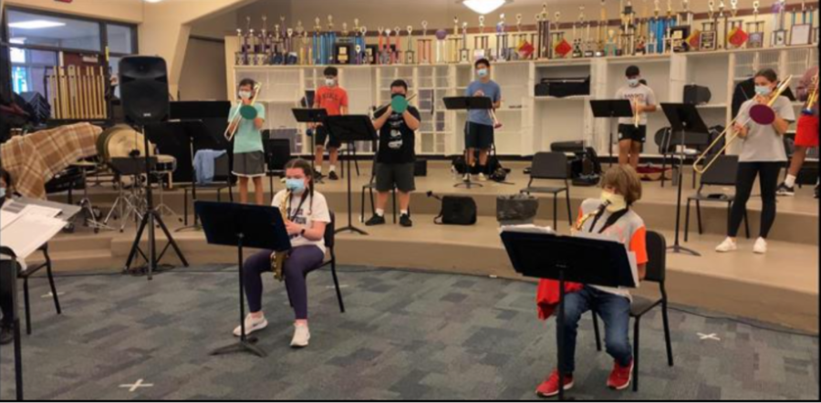 High school band students play their instruments in the band room. They are socially distanced with masks around their instruments.